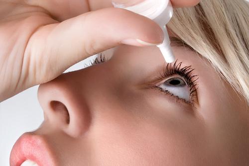 Kvinna applicerar ögondroppar i torra ögon
