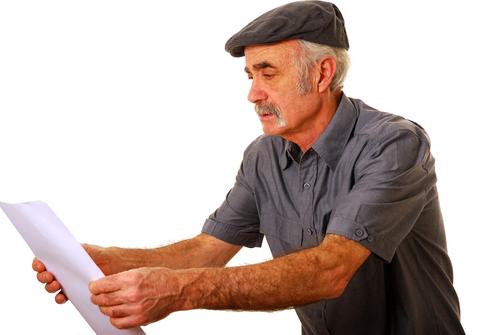 Översynt man försöker läsa på ett papper